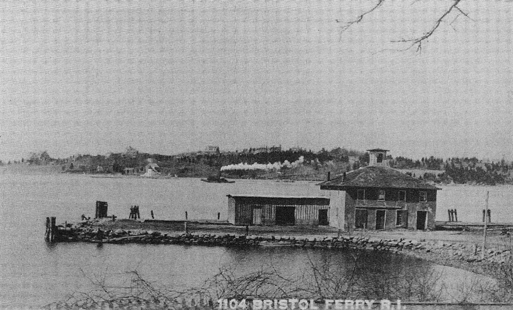 The steamboat wharf with its freight and passenger buildings. A pogey boat steams past in the background.