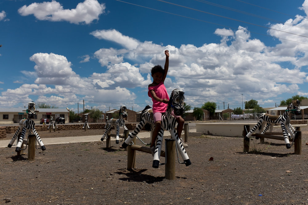 Beaufort West  A young girl plays in the park beside the N1 high-way.  Format: Hahnemuhle Photo Rag Size: 11.69 x 16.53 inches (A3) Signed, Edition of 20 Price increases as Edition sells R1800 (approx. $130)