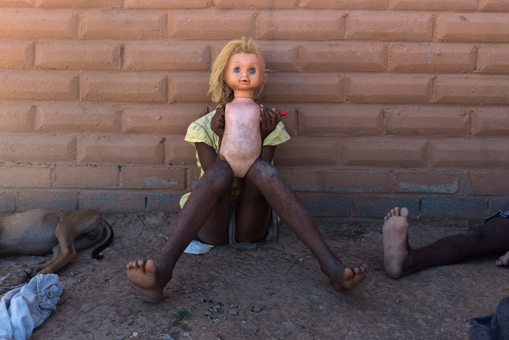 Philipstown  A young girl playing with her doll and friends outside of her RDP (Reconstruction and Development programme)  house.  Format: Hahnemuhle Photo Rag Size: 11.69 x 16.53 inches (A3) Signed, Edition of 20 Price increases as Edition sells R1800 (approx. $130)