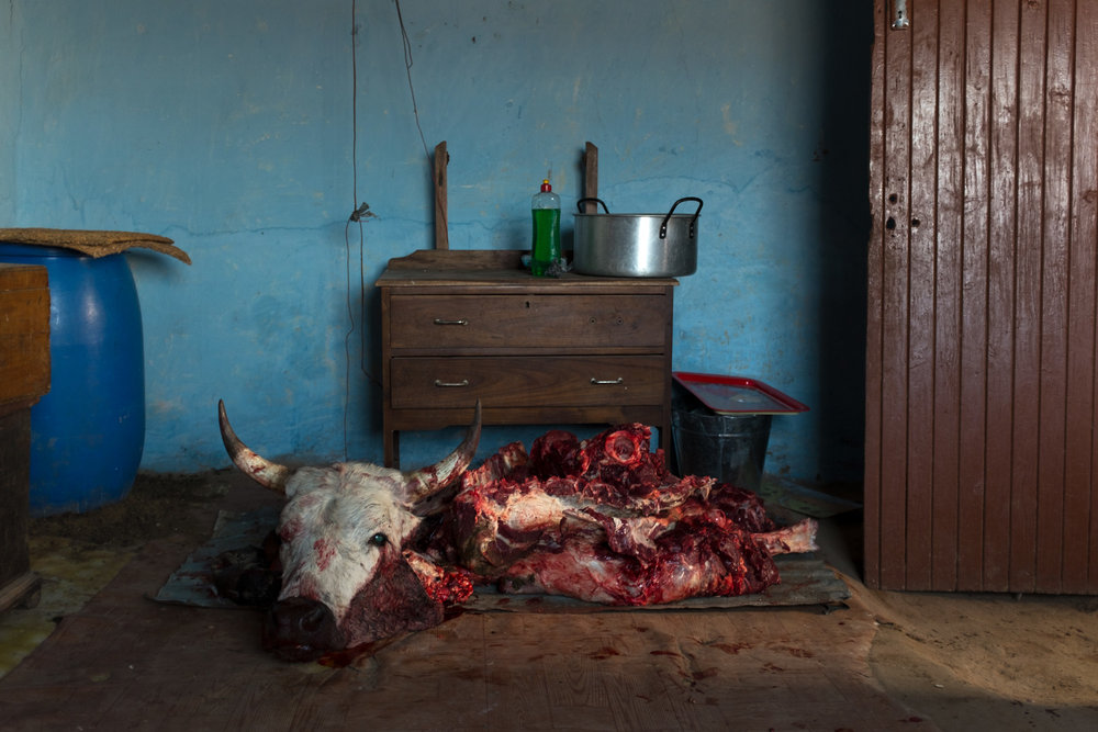 Qunu  The remains of a cow in the bedroom as the woman in the kitchen, next door, prepare the meat for the wedding ceremony.  Format: Hahnemuhle Photo Rag Size: 11.69 x 16.53 inches (A3) Signed, Edition of 5 (2 remain) Price increases as Edition sells R15000 (approx. $1090)