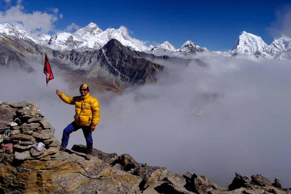 Our guide Sanu with a Nepalese flag claiming triumph