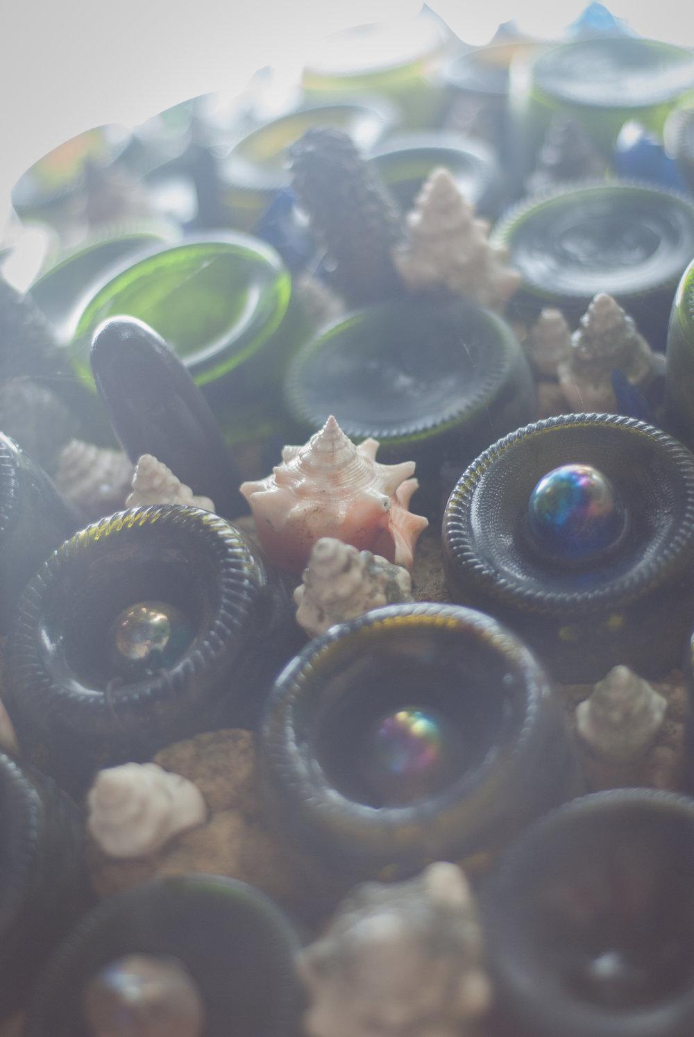 Platos y botellas enteros se amontonan uno sobre otro para crear la ilusión de árboles de Navidad de pan de jengibre. La concha y otras conchas marinas acentúan las formas eclécticas que se derraman de todas partes.
