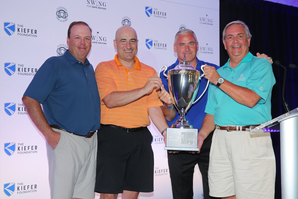 The wining team of the inaugural Swing for Safe Driving Ball Golf Tournament hoist the honorary Mitchel Kiefer Trophy.