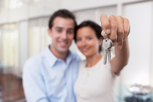 young couple holds up keys to new home