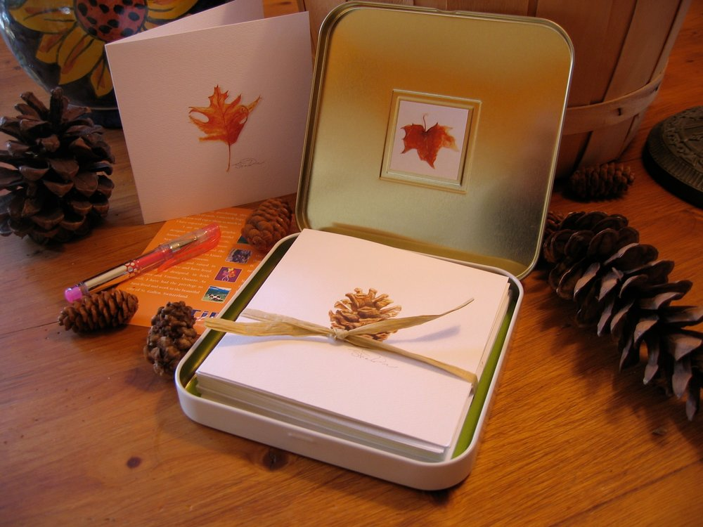 """Our unique gift tins are for any occasion. (1) white mother of pearl tin, (2) magnets, Artist bio, (8) 4.5"""" x 4.5"""" artist cards, (8) white wove envelopes, (1) mini gel pen, helpful hints for writing a note."""