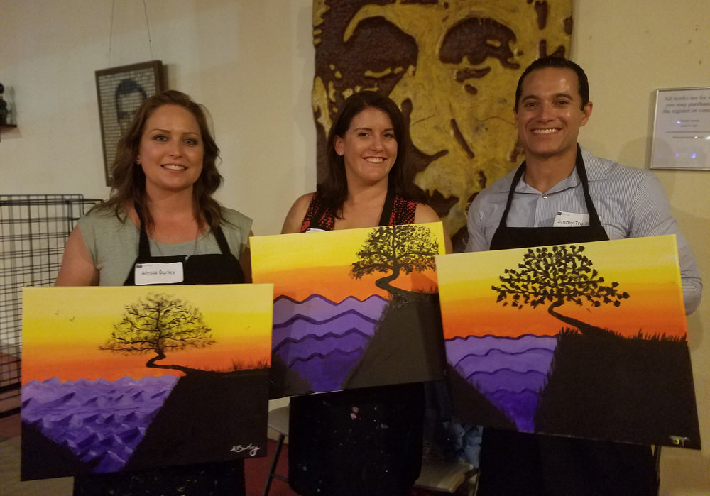 Alyssa Burley and Christina Haake from Rancho Mesa Insurance Services, and Jimmy Trujillo from  Imperial PFS  show off their finished paintings.