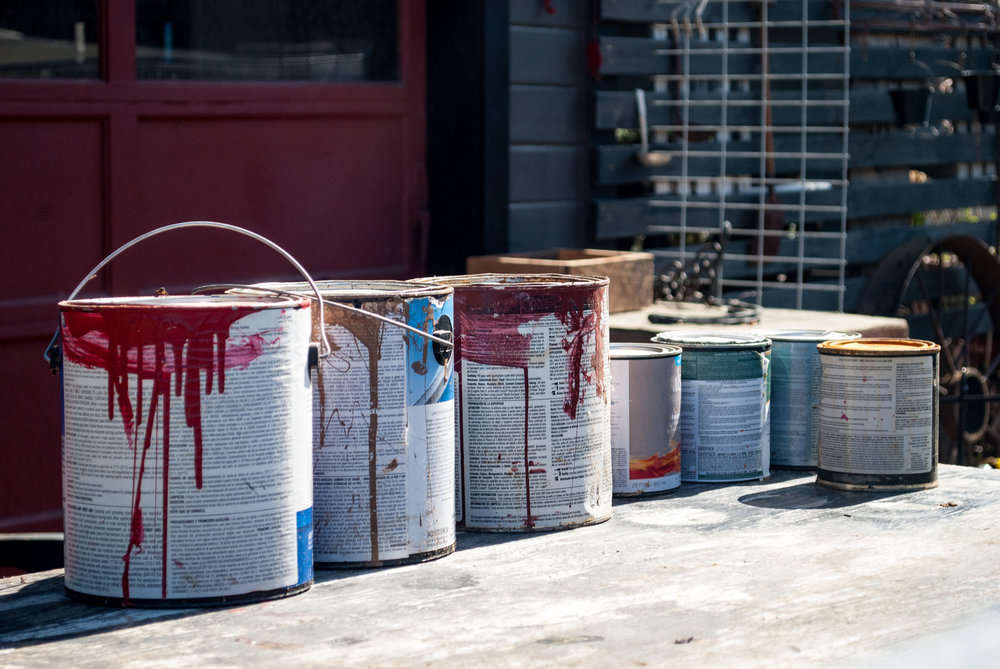 Several paint cans with paint dripping down sides