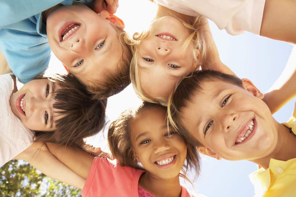Group of smiling children in a huddle looking down towards the camera lens.