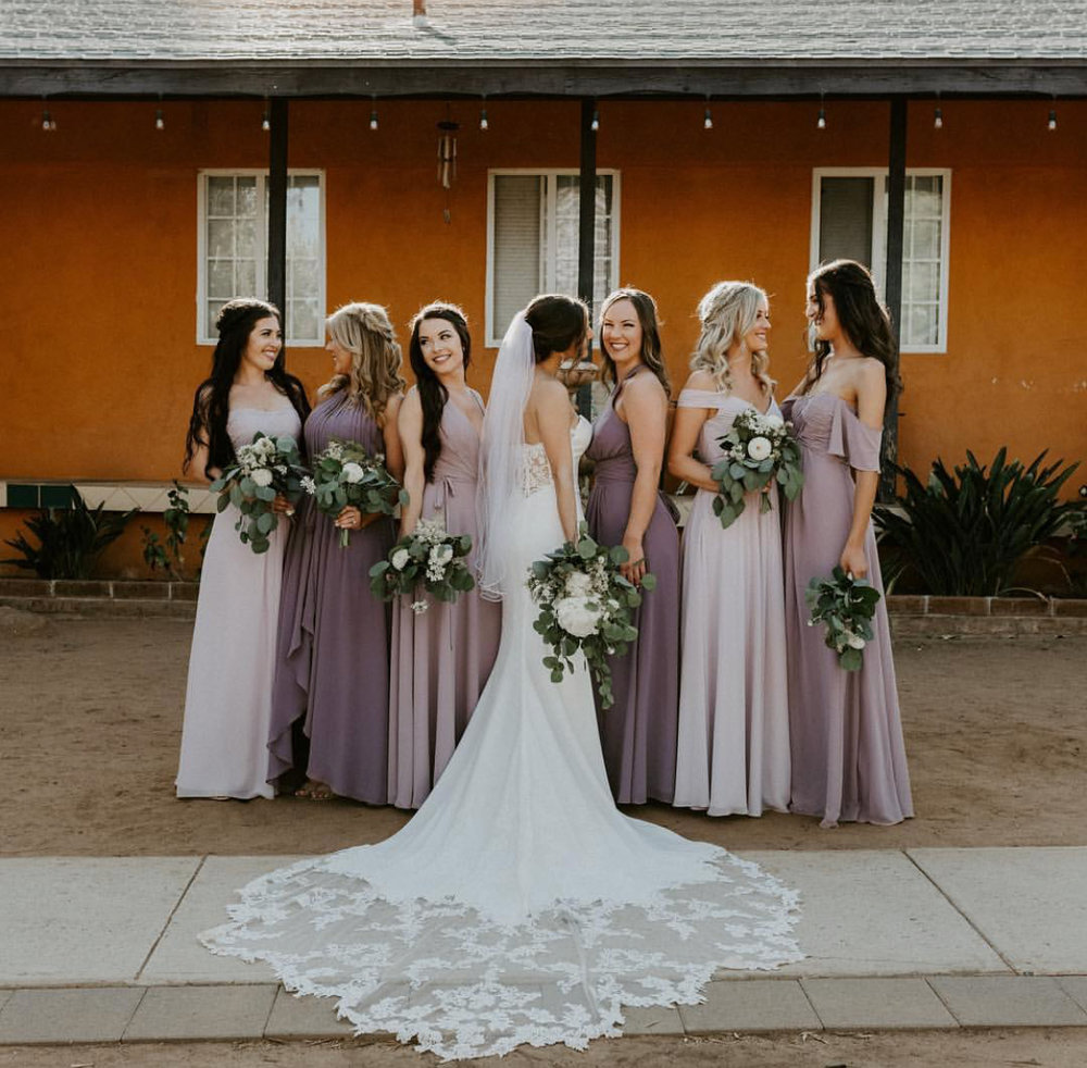 Six bridesmaids in various shades of lavender standing in a line with the bride's back to the camera to show off the train on the wedding dress.
