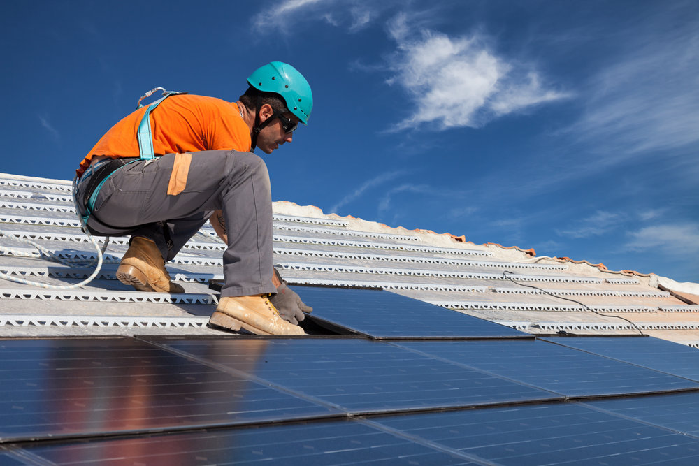 Man installing a solar panel on a roof.