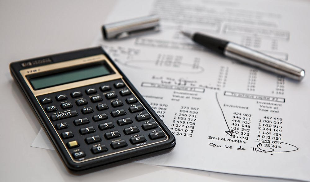 Calculator, a pen and financial documents on a table.