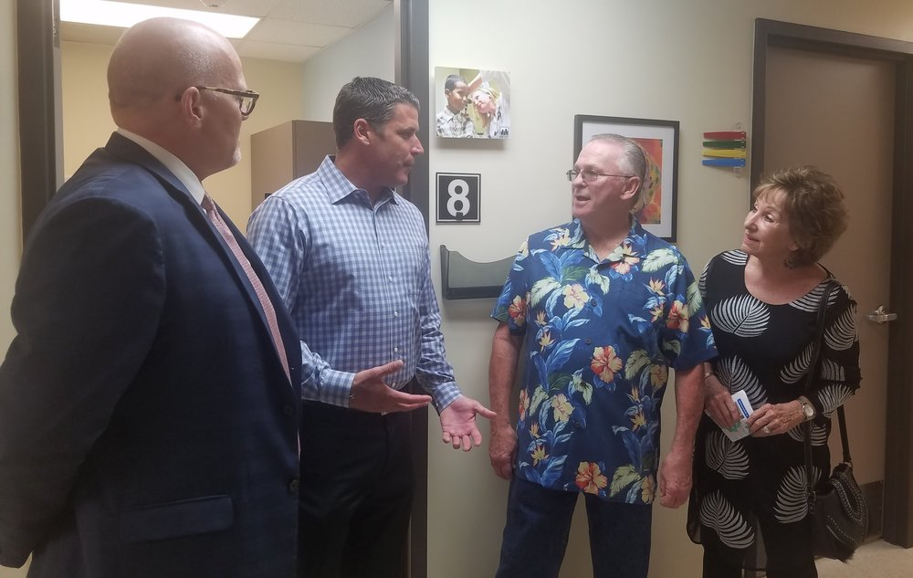 Anthony White, Sam Clayton, Tom and Debby Doyle talking in hallway in front of an examination room at Family Health Centers San Diego.