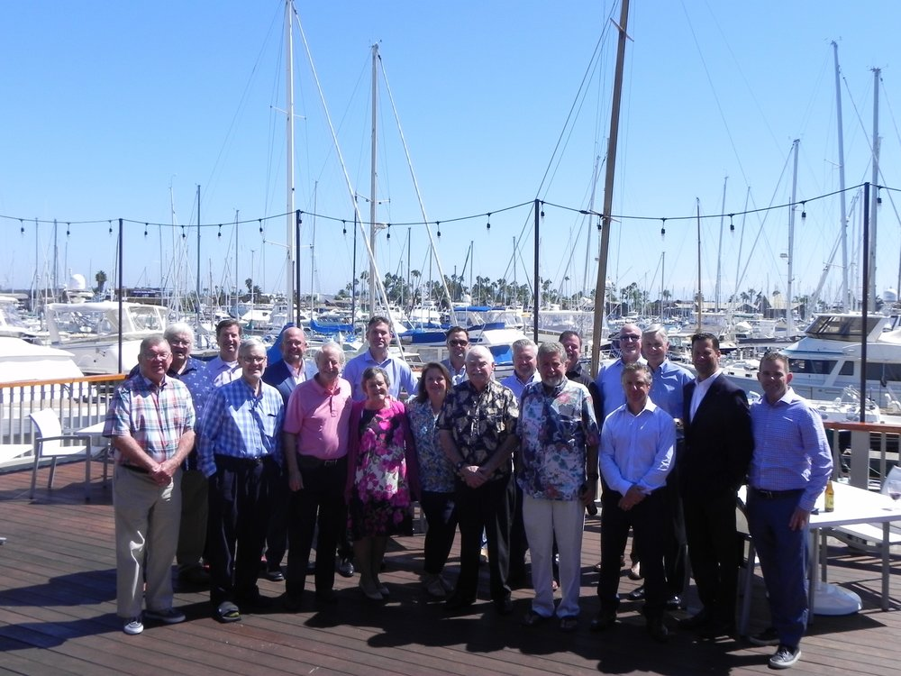 19 Past Presidents of the IIAB San Diego standing on a boardwalk at ta marina.