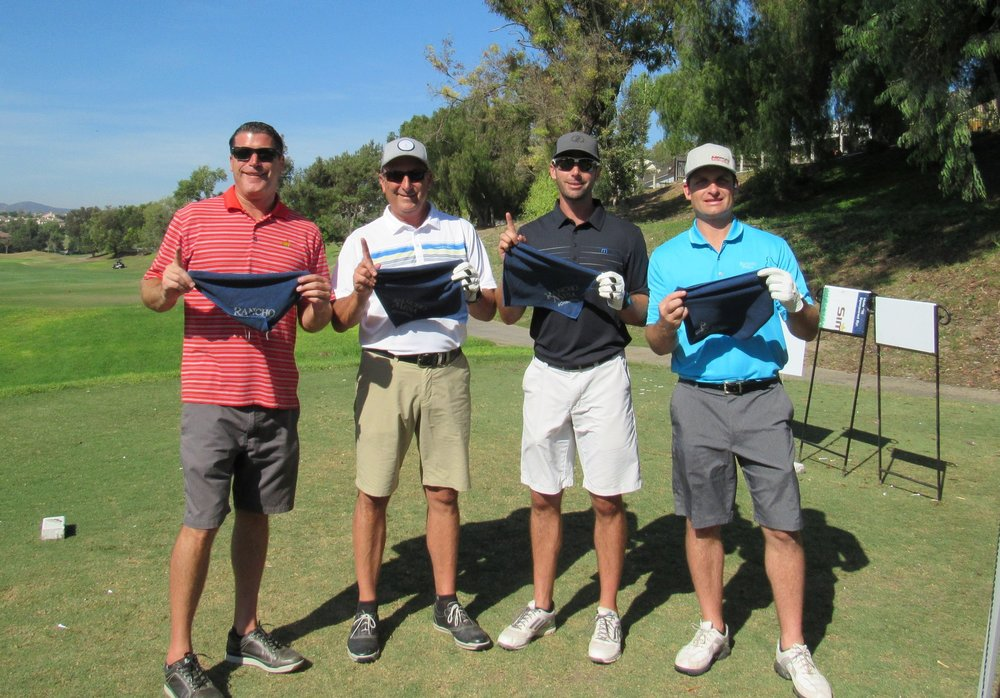 Sam Clayton, Dave Garcia, Drew Garcia and Kevin Howard holding Rancho Mesa golf towels showing a #1 with their fingers.