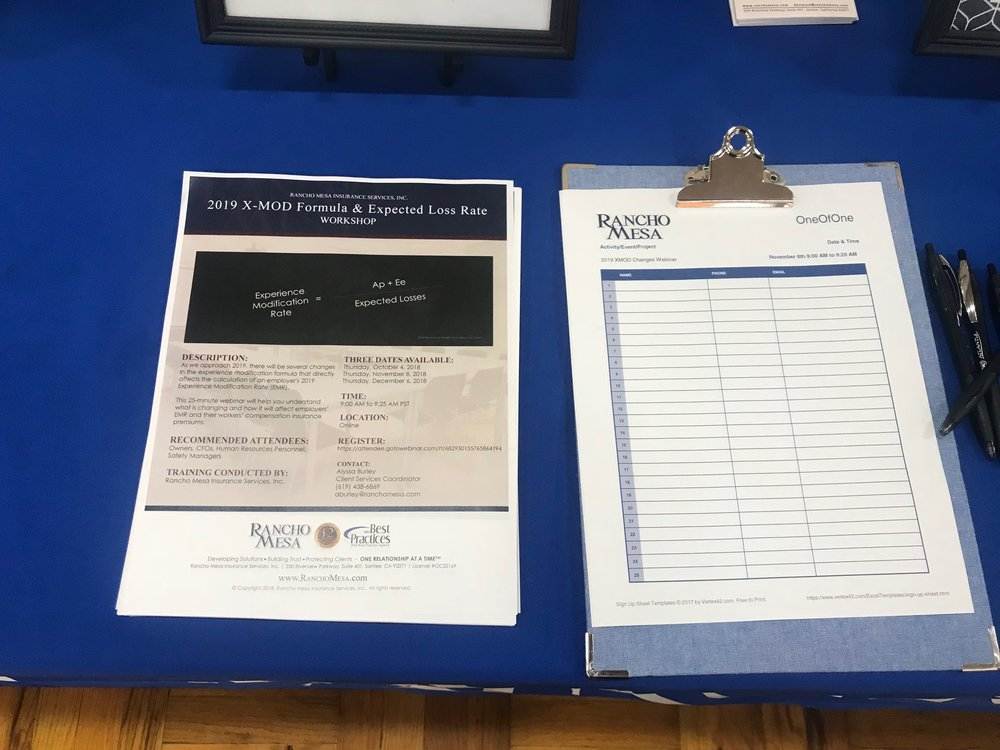 A flyer for the upcoming webinar and a clipboard with an empty sign in sheet laying on a table.