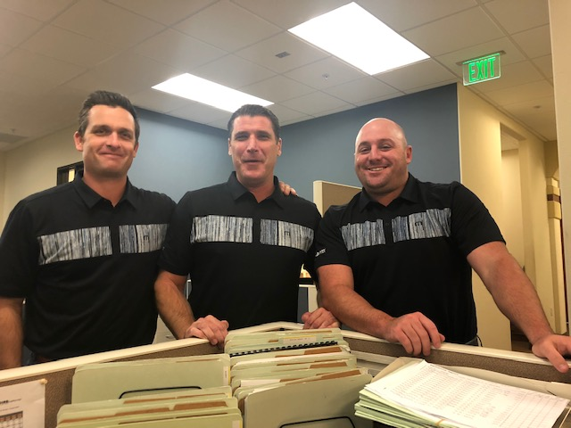 Kevin Howard, Sam Clayton, and Casey Craig wearing the same black golf shirt with a grey horizontal stripe.