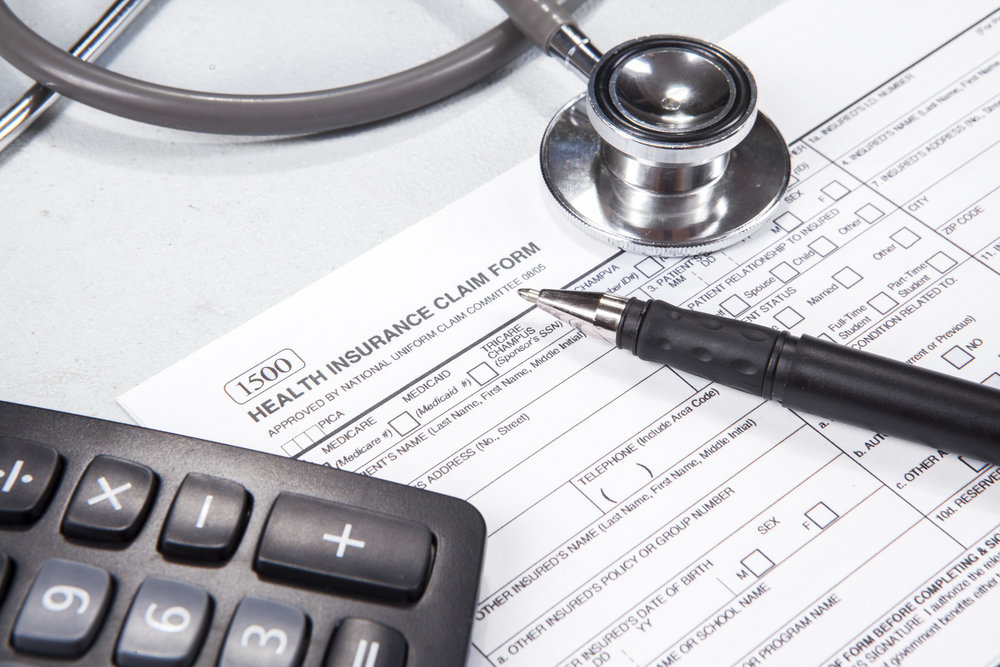 Health Insurance Claim Form, calculator, pen and stethoscope.