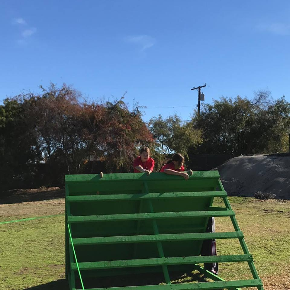 Trinity Restine and Kaia Hoolihan  climbing over a wall in the obstacle course.