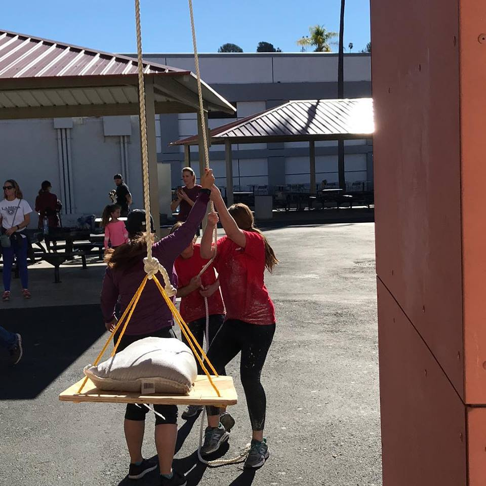 Trinity Restine and Kaia Hoolihan using a hoist (with a spotter) to lift a sandbag as a task in the obstacle course.