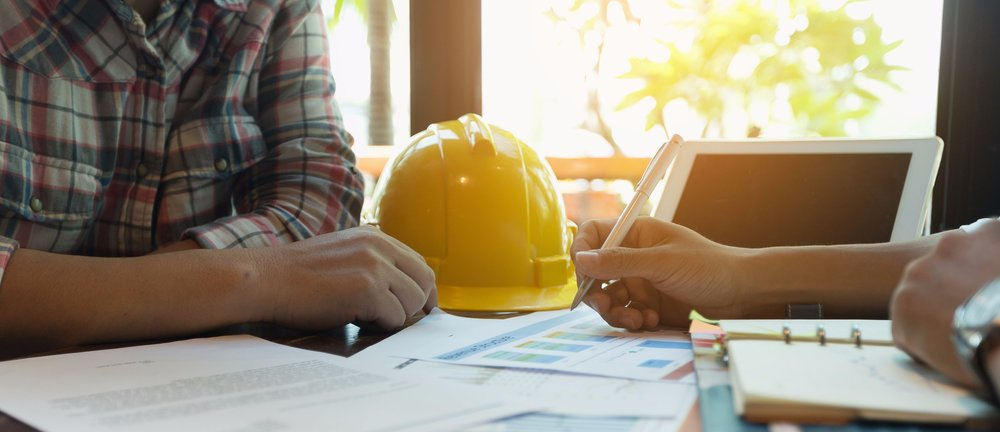 2 people at table with papers and hardhat