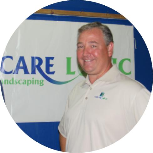 Craig Gerber standing in front of a Landcare Logic banner.
