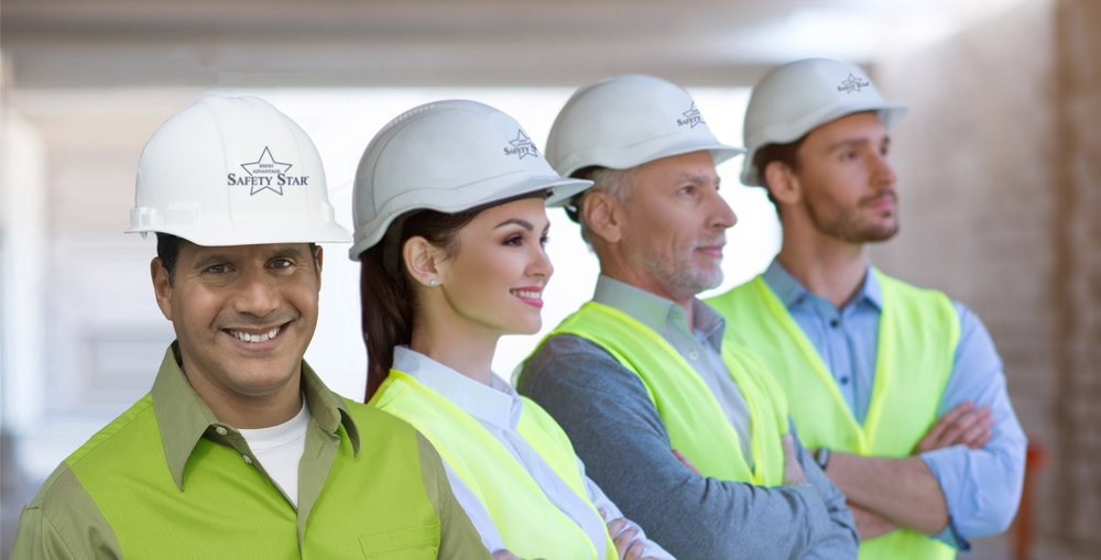 Three men and a women standing in a row wearing hard hats with Safety Star logo the hat.