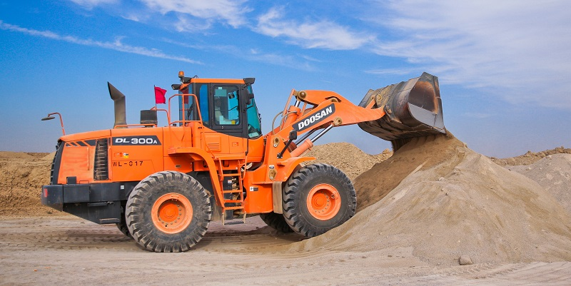 Image of large orange tractor moving piles of dirt