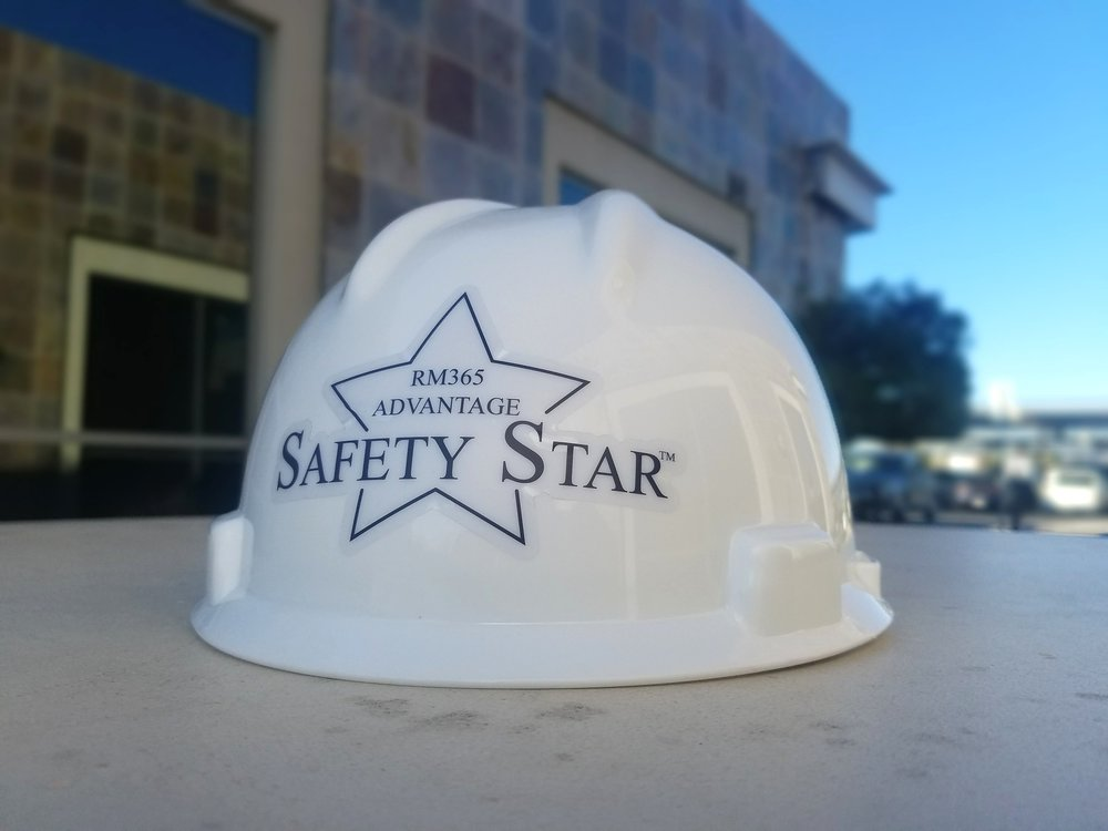 White hard hat sitting on an outdoor concrete table with a RM365 Advantage Safety Star sticker on the back.