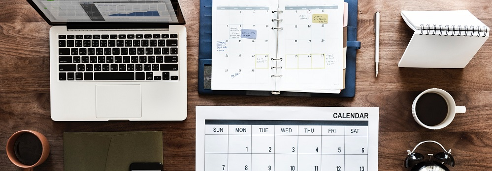 Image of calendar, planner, laptop, and coffee on desk