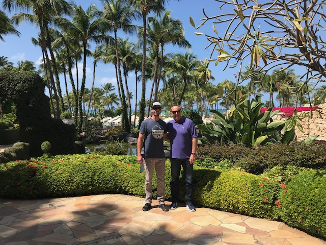 Drew and Dave Garcia smiling in a tropical setting