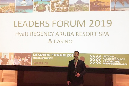 Drew Garcia standing in front of the giant Leaders Forum 2019 screen