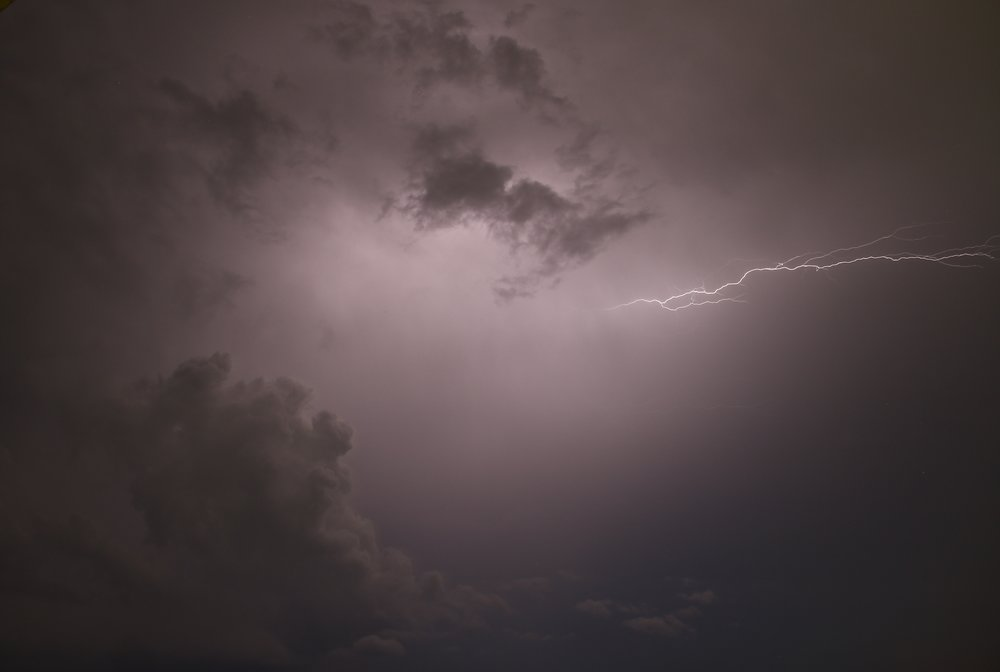 A lightning bolt shoots out from behind grey and purple clouds.