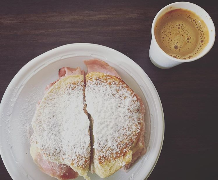 Image of a Mallorca filled with ham and cheese and coated with powdered sugar, next to a cup of café con leche