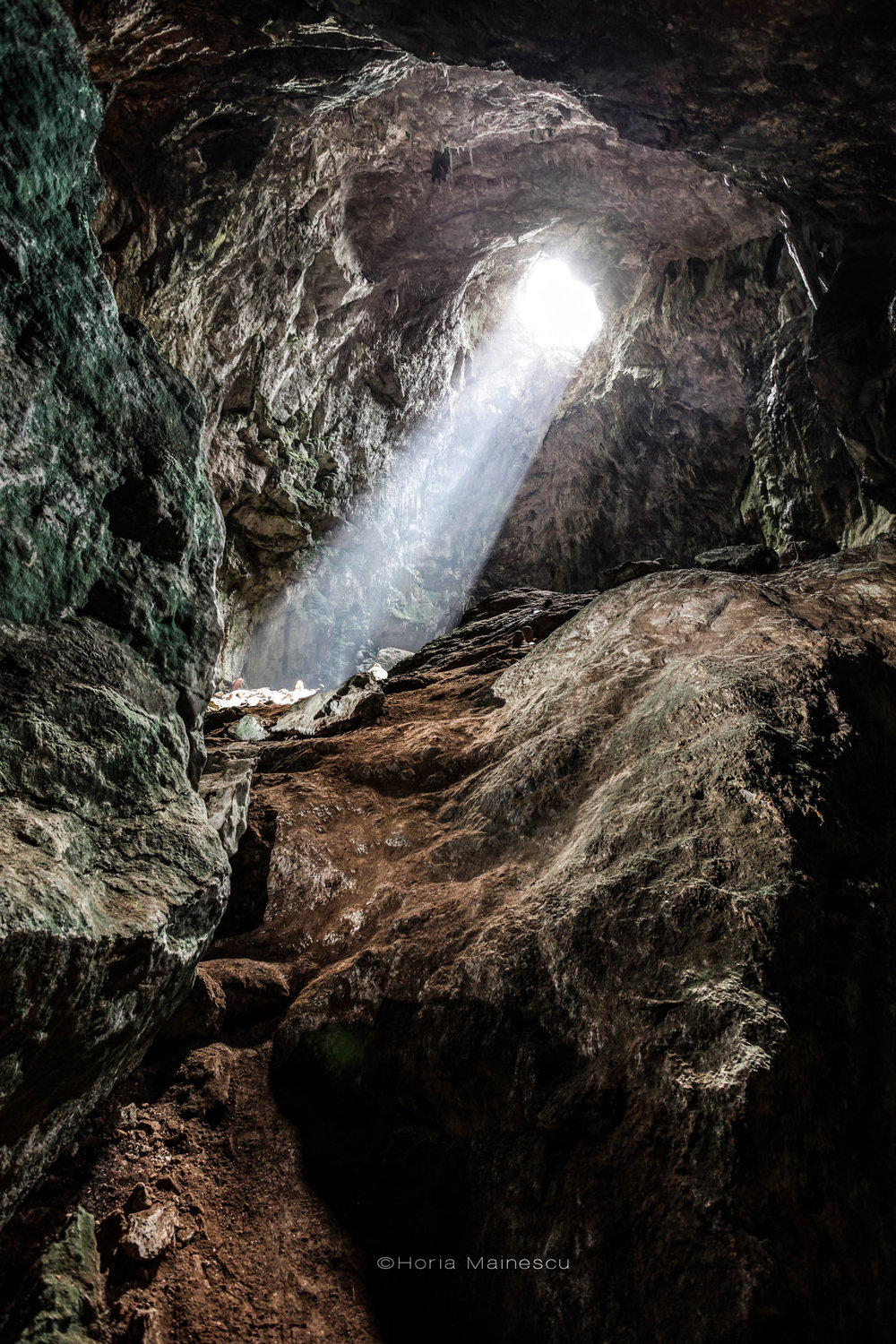 The cave is illuminated by natural light entering it through a hole located on the upper part.