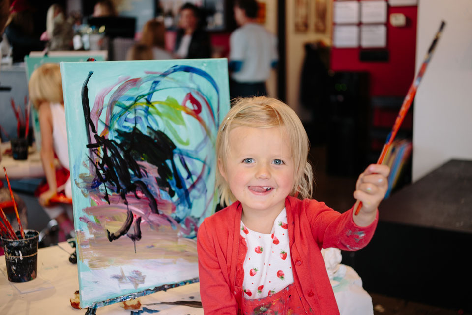 Child painting with brush and easel.