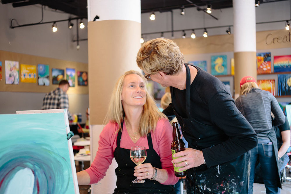 Couple at a paint mixer, drinking wine and beer while painting