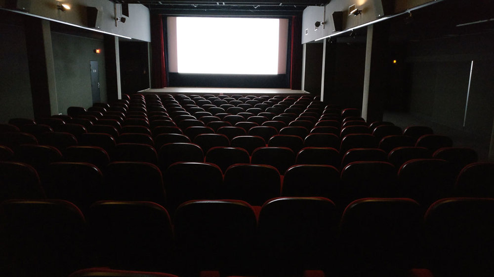 Empty theater with screen reflecting off the seats.