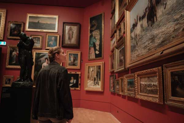 a young woman viewing art in an art gallery