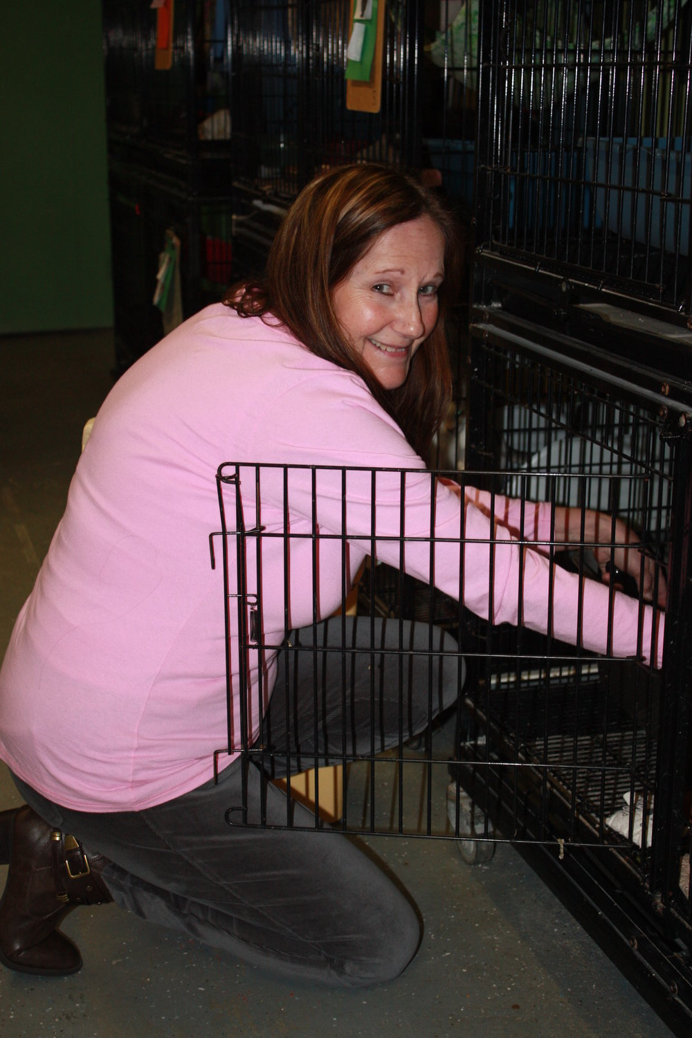 Margo, cleaning one of our  many cat units keeping there temporary home clean and keeping our babies happy and healthy.