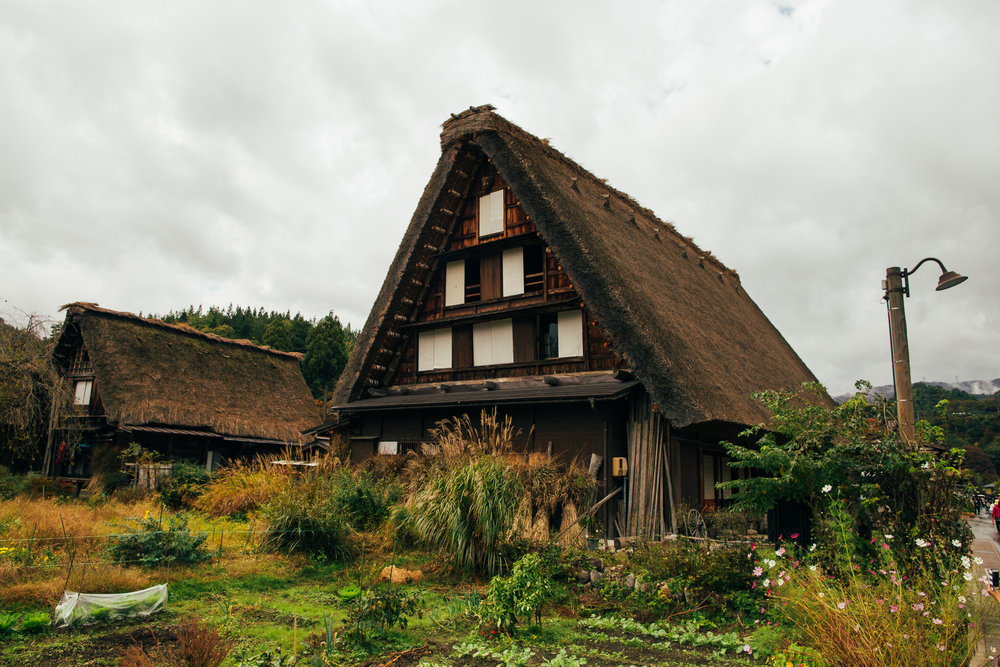 A private house. The roofs will actually feature slopes across various villages in the general region due to the varying amounts of snow they receive. These houses were traditionally farmers' homes so it is not surprising to find crops/plants being planted right next to the buildings.