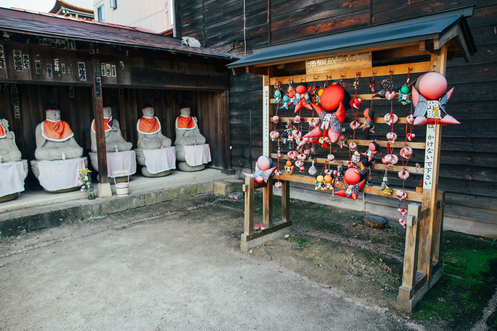 The red dolls you see on the right side of the photo are known as Sarubobo and are associated with Takayama. They are dolls given to grandchildren by grandmothers wishing them successful marriages and healthy offspring. Over the years, the Sarubobo doll has been 'modernized' with different colours representing different wishes (studies, career, health, money, etc.). That said, the red one is still the prevailing colour you will see in most gift shops, shrines and tourism centres.