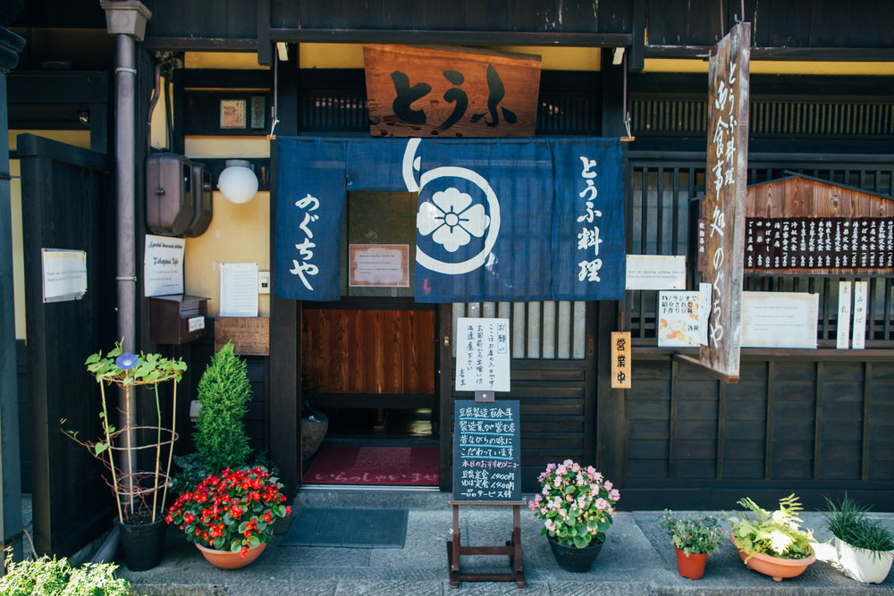 Shops in the old town of Takayama use traditional noren at their entrances. I think it's safe to assume that one segment flipped up means they are open for business.