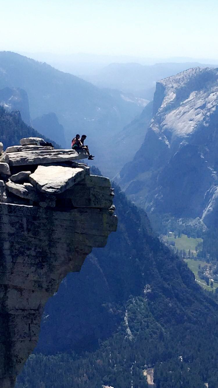 A picnicking couple sitting atop Visor Rock and the view of Yosemite Valley down below