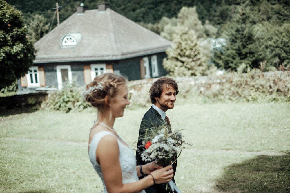 Glückliches Brautpaar läuft auf Wiese vor Haus