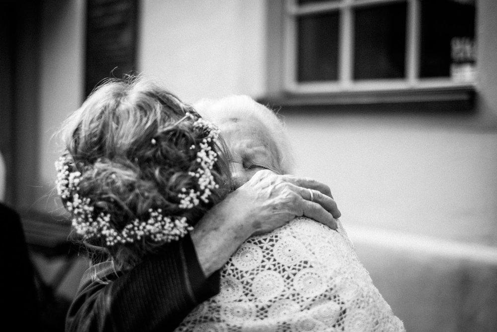 Gerührte Oma umarmt Braut in Burbach nach Zeremonie