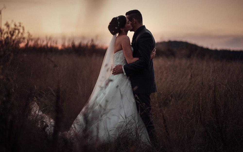 Hochzeitspaar beim Paarshooting mit toller Lichtstimmung während der Abenddämmerung auf einem Kornfeld.