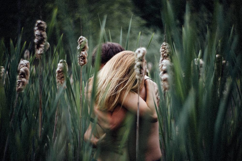 Paar beim Verlobungsshooting zwischen Gräsern in der Natur eng umschlungen den Moment genießend.