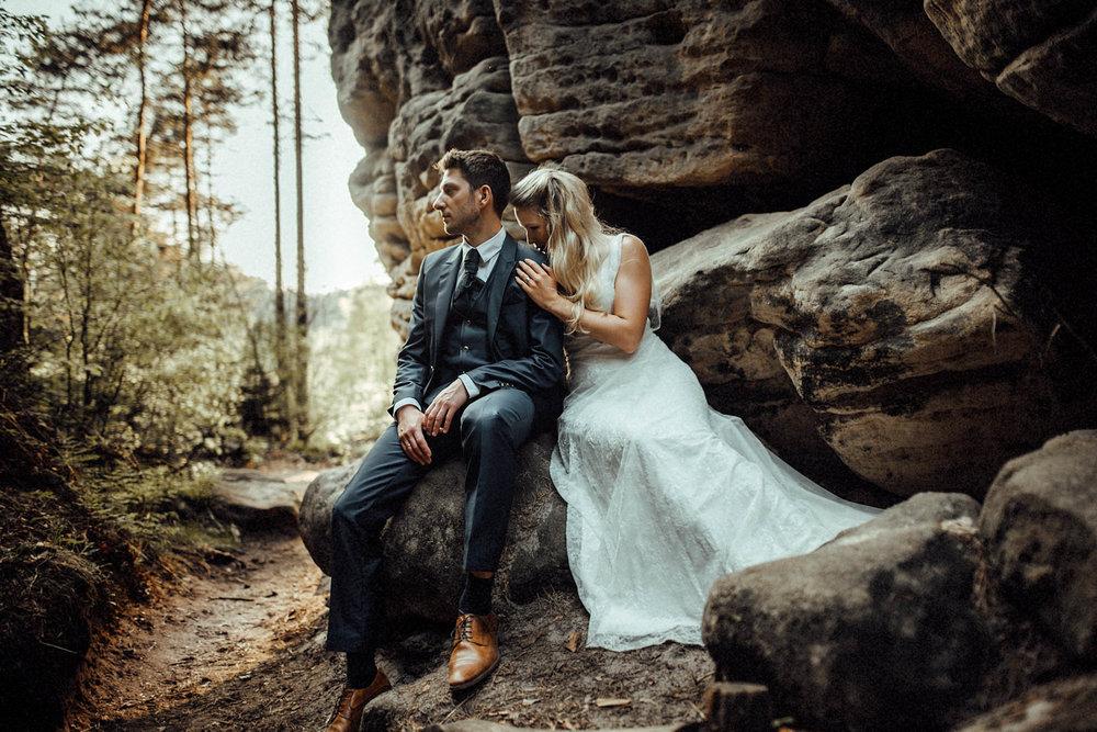Das Foto zeigt das Hochzeitspaar beim After Wedding Elopement Shooting ind er Böhmischen Sächsischen Schweiz beim grandiosen Sonnenuntergang zwischen Felsen.