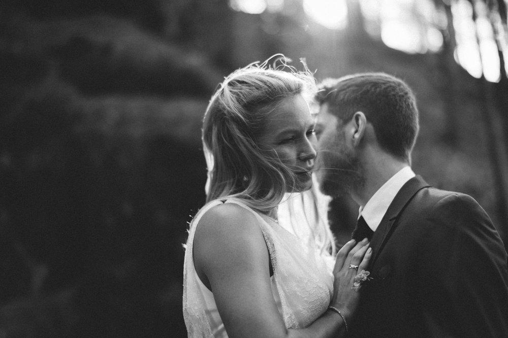 Das Schwarzweiß Foto zeigt das bezaubernde Hochzeitspaar bei Gegenlicht im Wald