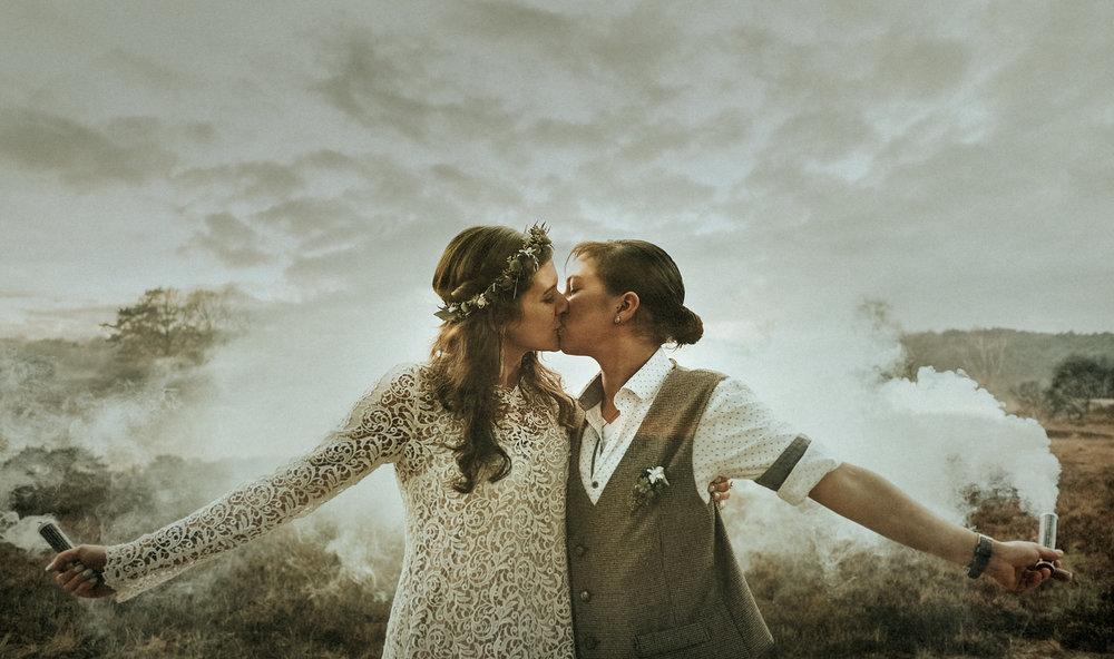 Alternatives gleichgeschlechtliches Hochzeitspaar sich küssend beim Paarshooting mit Rauchfackeln in der Natur.